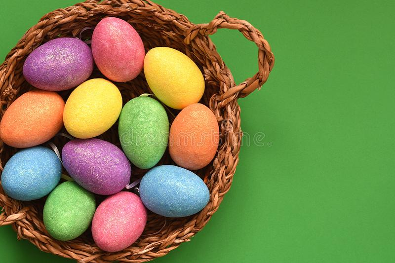 Huevos de Pascua coloreados chispeantes del caramelo que brillan en una cesta de mimbre, visión superior, fondo verde foto de archivo libre de regalías