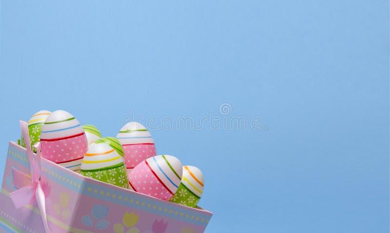 Huevos de Pascua coloreados en colores en colores pastel de la cesta de papel en fondo azul Tema de Pascua foto de archivo