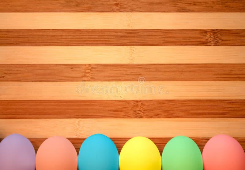 Huevos de Pascua coloreados en colores pastel en un fondo de madera imagenes de archivo