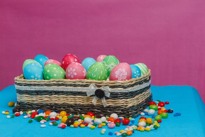 Huevos de Pascua coloreados en una cesta en un fondo azul-rosado fotos de archivo