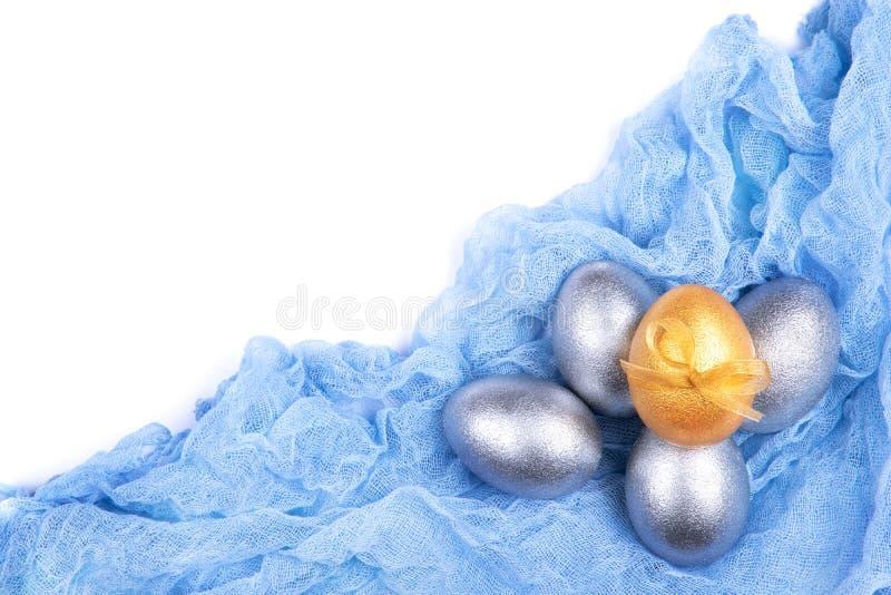 Huevos de Pascua coloreados de plata y de oro en la tela azul clara de la gasa aislada en el fondo blanco Visión superior Lugar p foto de archivo