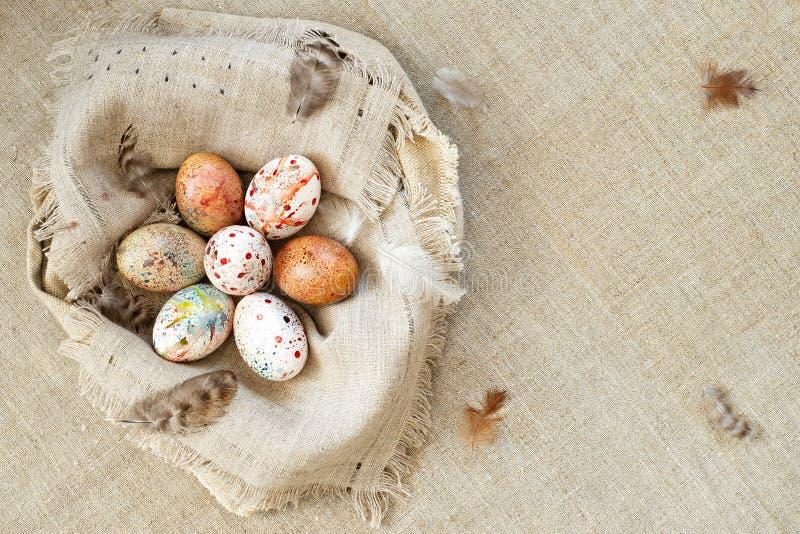 Huevos de Pascua coloridos brillantes en una jerarquía de la tela de la lona fotos de archivo