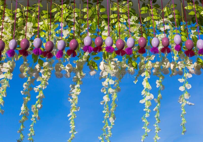 Huevos de Pascua coloridos colgantes y decoración floral en un fondo del cielo azul fotografía de archivo libre de regalías