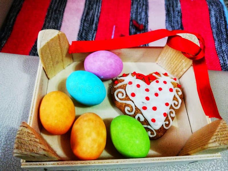 Huevos de Pascua coloridos con el postre adornado del corazón, decoración para Pascua, imagen de archivo