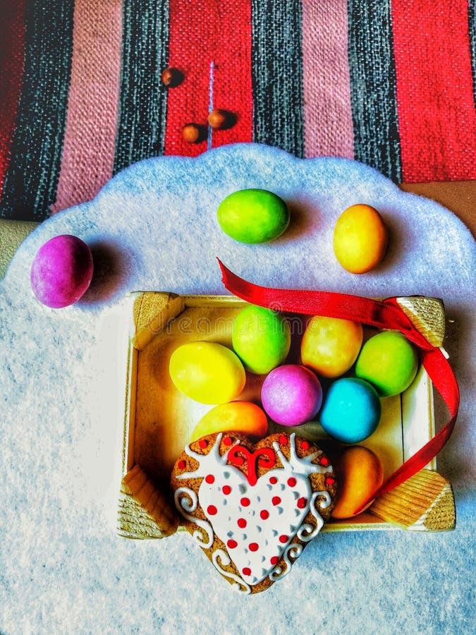 Huevos de Pascua coloridos con el postre adornado del corazón, decoración para Pascua, imagen de archivo libre de regalías