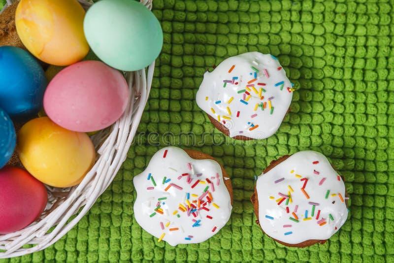 Huevos de Pascua coloridos en cesta y magdalenas dulces del mollete Fondo de Pascua Concepto de pascua del día de fiesta religios fotografía de archivo libre de regalías
