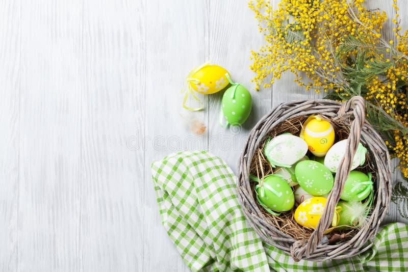 Huevos de Pascua coloridos en cesta y mimosa imagen de archivo
