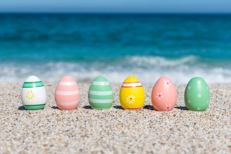 Huevos de Pascua coloridos en la playa en día soleado foto de archivo