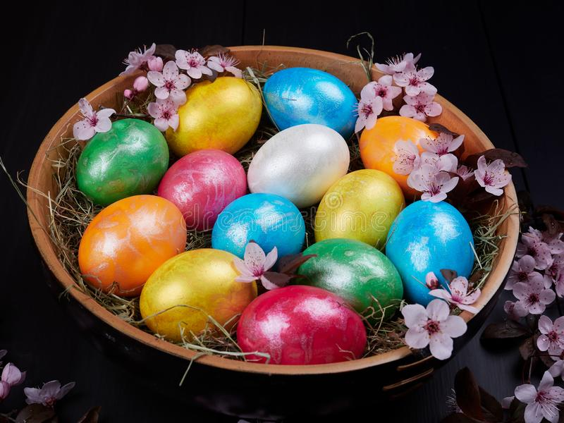 Huevos de Pascua coloridos en un cuenco de madera fotografía de archivo