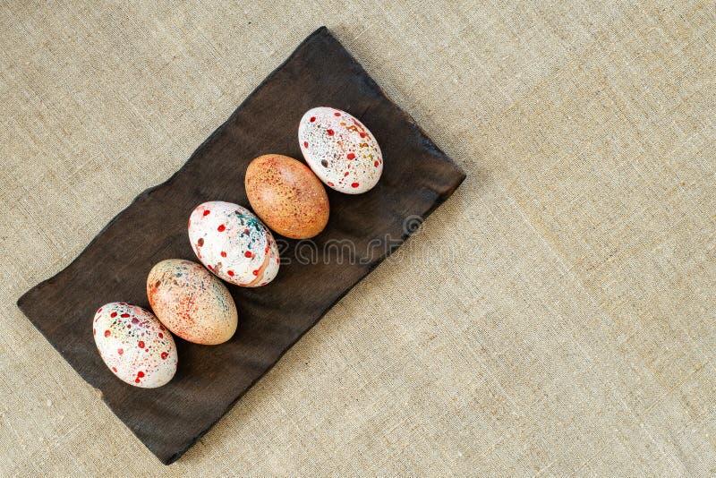 Huevos de Pascua coloridos en un tablero de madera quemado en lona fotos de archivo