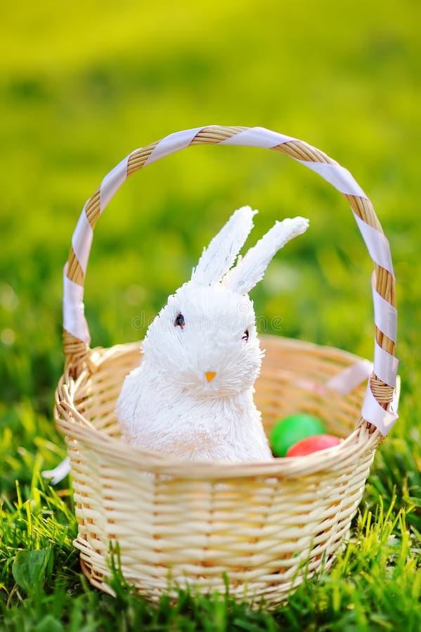 Huevos de Pascua coloridos en una cesta con el conejito blanco lindo del juguete foto de archivo
