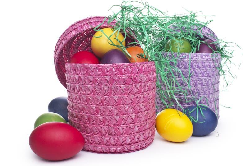 Huevos de Pascua coloridos en una cesta en los gras imágenes de archivo libres de regalías