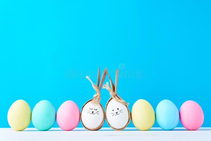 Huevos de Pascua con las caras pintadas en fila en un fondo azul fotos de archivo