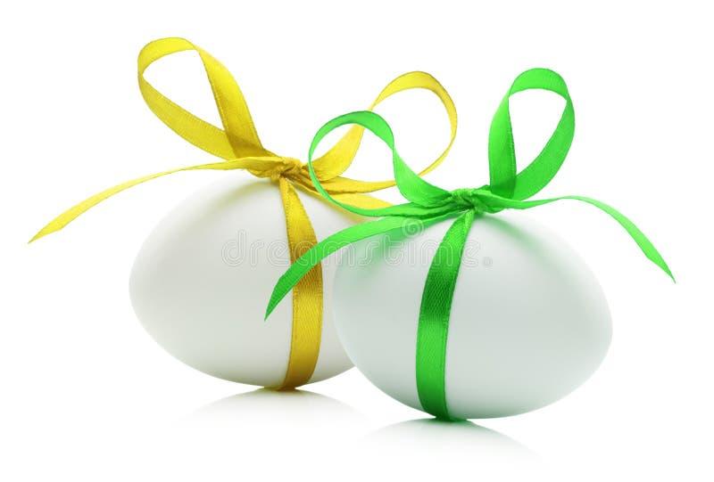 Huevos de Pascua con las cintas amarillas y verdes aisladas en el blanco imagen de archivo