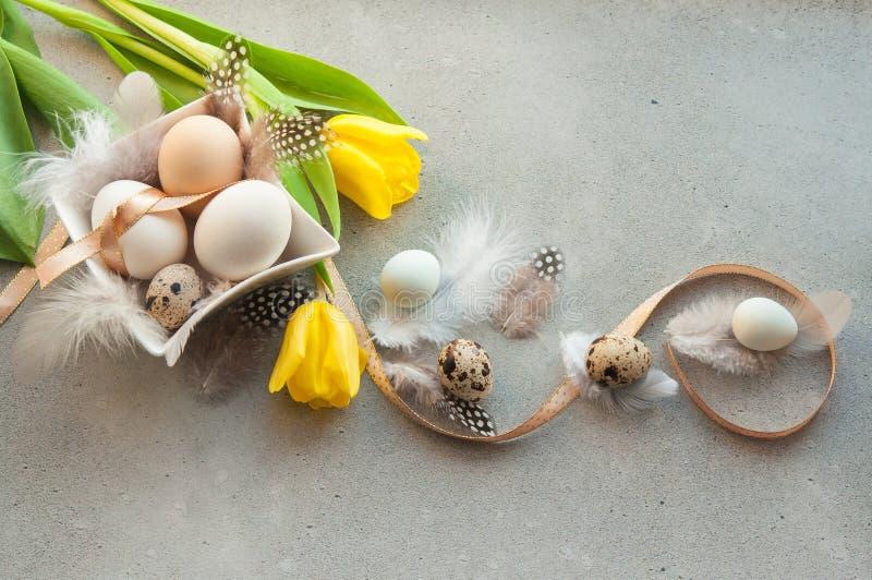 Huevos de Pascua con las flores y las plumas fotos de archivo