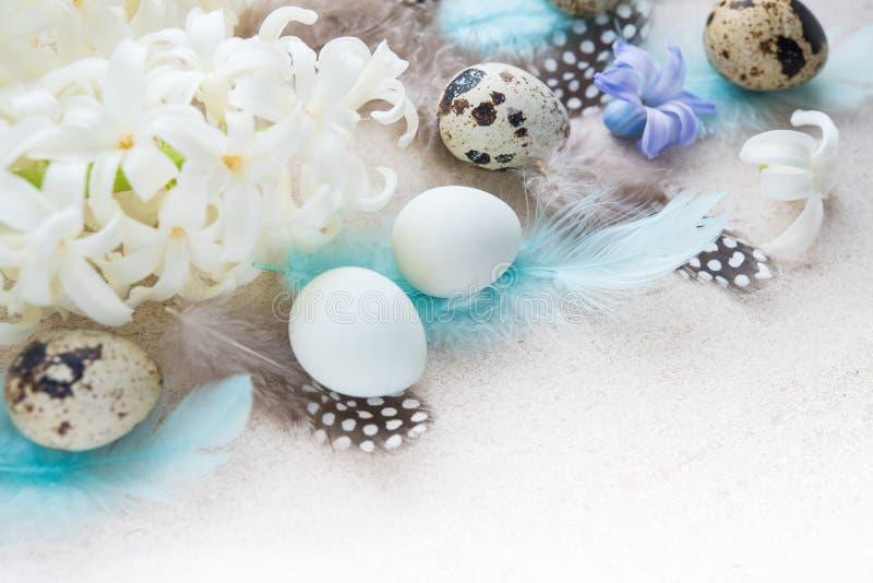 Huevos de Pascua con las flores y las plumas foto de archivo