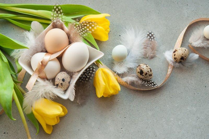 Huevos de Pascua con las flores y las plumas imagenes de archivo