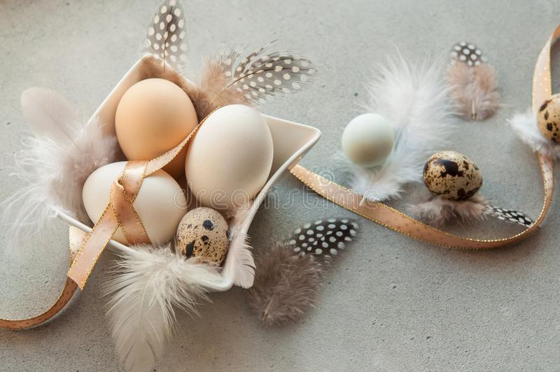 Huevos de Pascua con las flores y las plumas fotografía de archivo