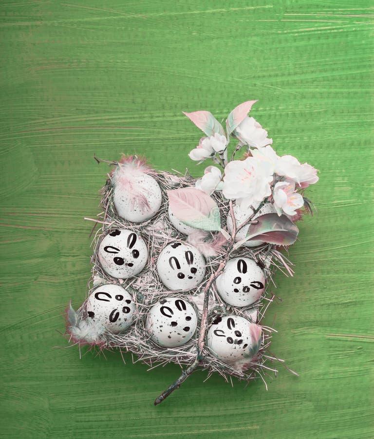 Huevos de Pascua con los conejos de conejito pintados en el fondo verde, visión superior fotos de archivo