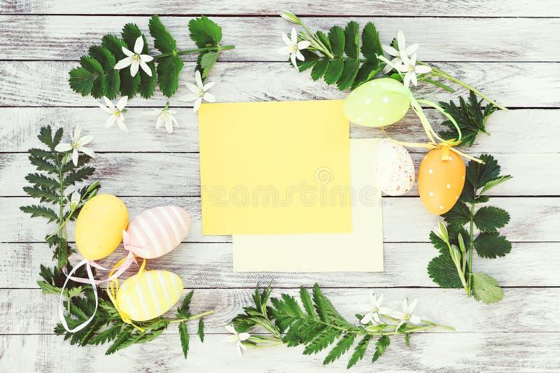 Huevos de Pascua con los ornamentos florales alrededor Flores de la primavera, huevos, tarjeta vacía en fondo de madera Maqueta d imágenes de archivo libres de regalías