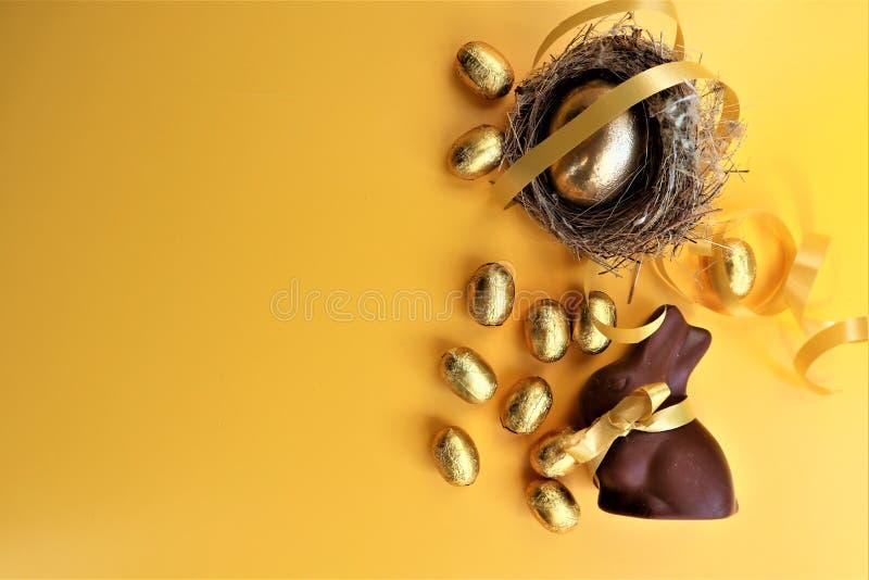 Huevos de Pascua del chocolate y conejito de oro del chocolate en un fondo amarillo imagenes de archivo