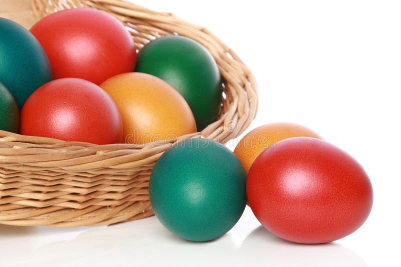 Huevos de Pascua del color en una cesta wattled fotos de archivo
