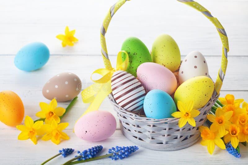Huevos de Pascua en canasta y flores daffodiales de primavera sobre mesa de madera blanca fotos de archivo