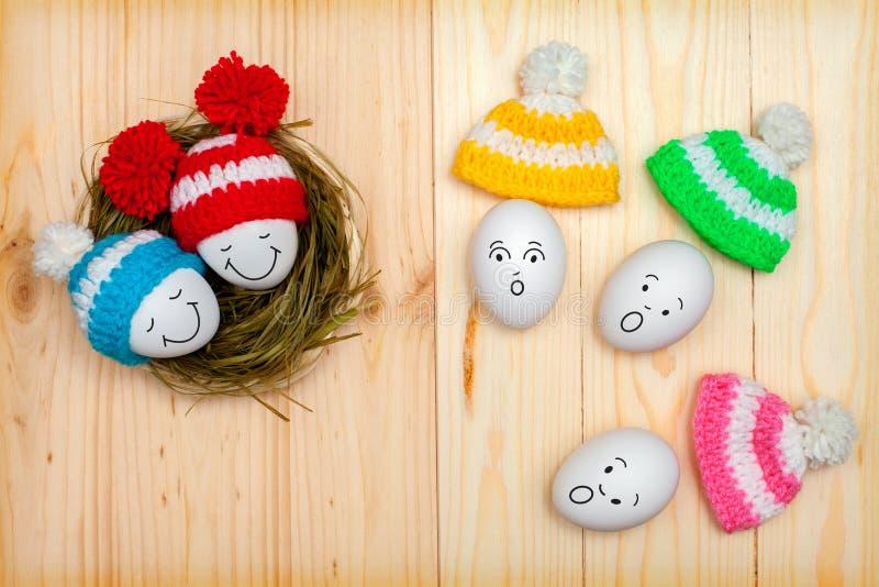 Huevos de Pascua en casquillos coloreados en una tabla de madera, con emociones del rostro humano imagenes de archivo