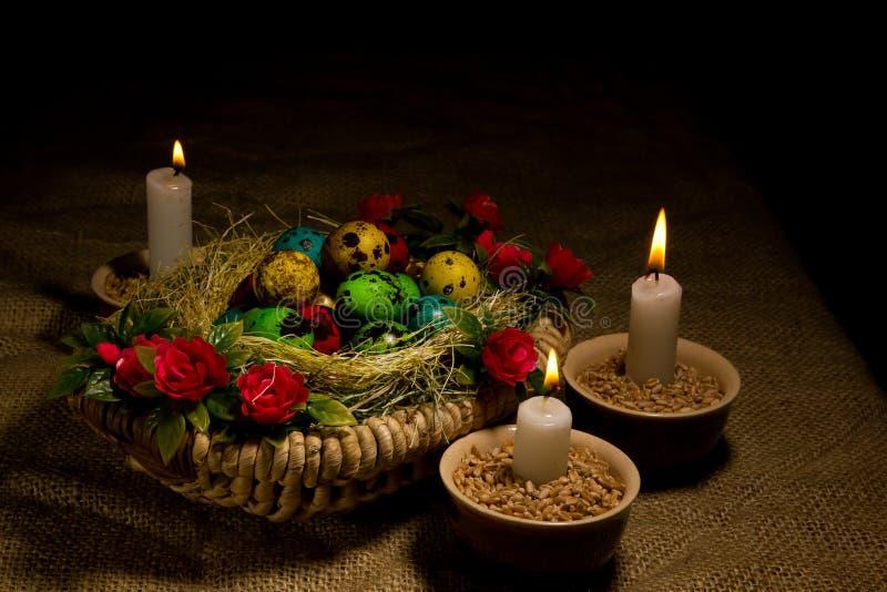 Huevos de Pascua en cesta de madera con las velas de Pascua foto de archivo