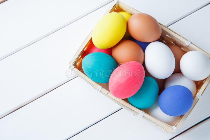 Huevos de Pascua en cesta en la tabla de madera Pascua feliz foto de archivo libre de regalías