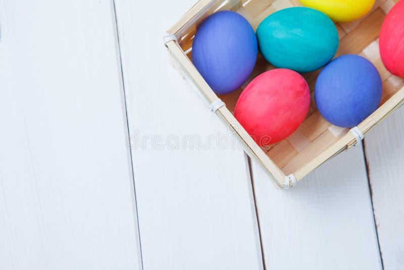 Huevos de Pascua en colores pastel y coloridos en cesta Pascua feliz foto de archivo