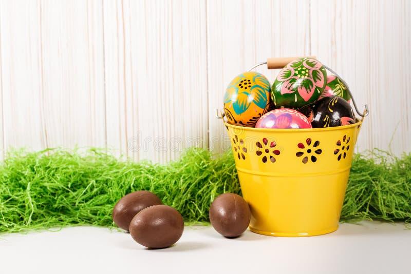 Huevos de Pascua en cubo en fondo de madera con la hierba verde imagenes de archivo