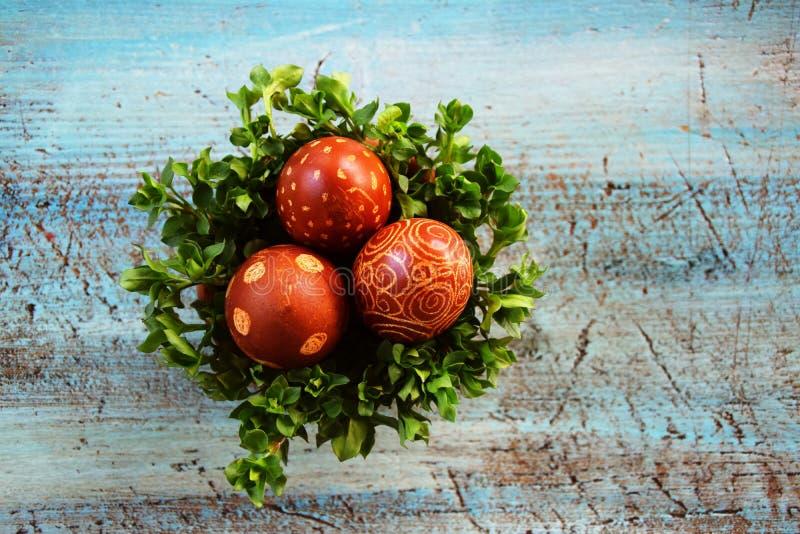 Huevos de Pascua en cuenco en el escritorio azul fotografía de archivo