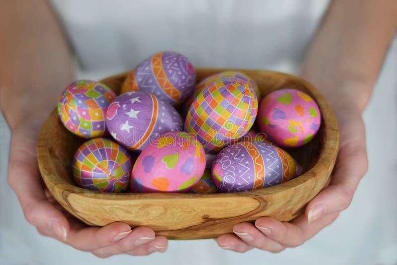 Huevos de Pascua en cuenco en manos de la mujer foto de archivo