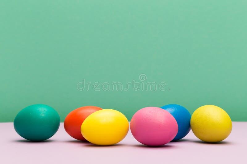 Huevos de Pascua en el fondo del color - imagen imagenes de archivo