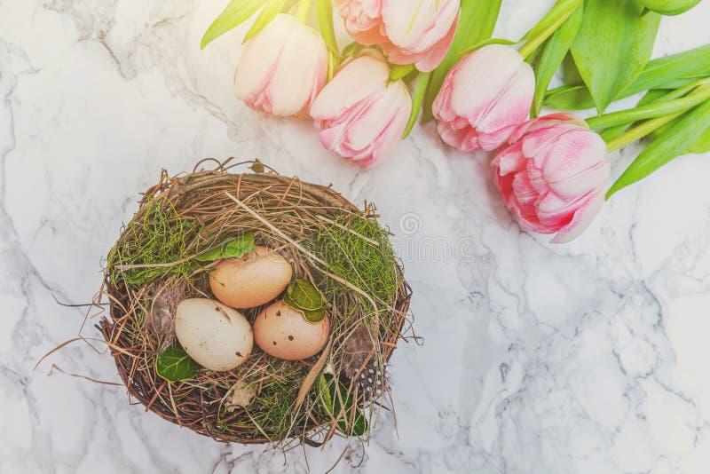 Huevos de Pascua en jerarquía con el musgo y ramo fresco rosado del tulipán en el fondo de mármol fotos de archivo libres de regalías