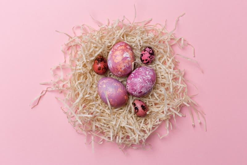 Huevos de Pascua en jerarquía en fondo rosado Textura de Pascua imagen de archivo