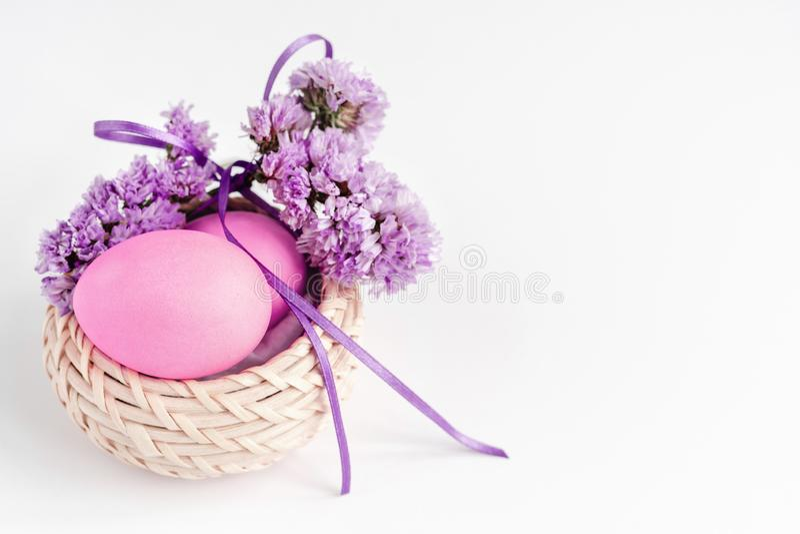 Huevos de Pascua en la cesta adornada con las flores en tonos de la lila en el fondo blanco Tarjeta de felicitaci?n imagen de archivo libre de regalías