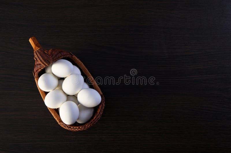 Huevos de Pascua en la cesta del pato cesta de mimbre de paja comida festiva en una tabla de madera oscura fotografía de archivo