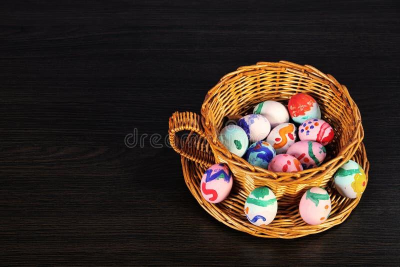 Huevos de Pascua en la cesta cesta de mimbre de paja comida festiva en una tabla de madera oscura foto de archivo