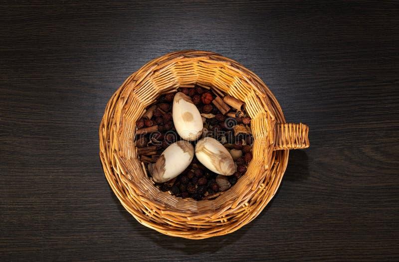 Huevos de Pascua en la cesta cesta de mimbre de paja comida festiva en una tabla de madera oscura imagenes de archivo