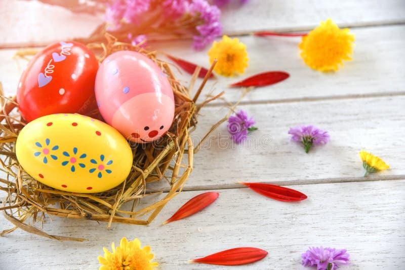 Huevos de Pascua en la decoración de la jerarquía con el fondo blanco de la primavera del pétalo colorido de las flores fotos de archivo libres de regalías