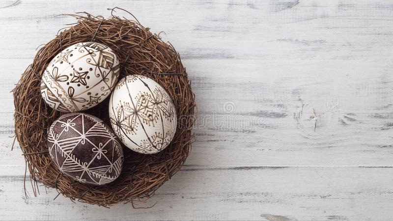 Huevos de Pascua en la jerarquía en fondo de madera fotos de archivo