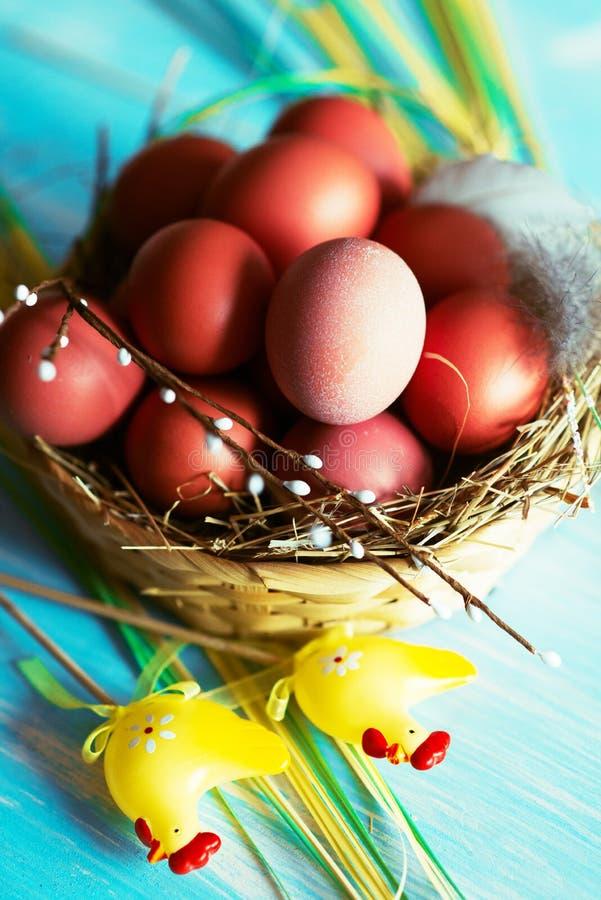 Huevos de Pascua en la jerarquía, preparándose en fondo de madera azul foto de archivo libre de regalías