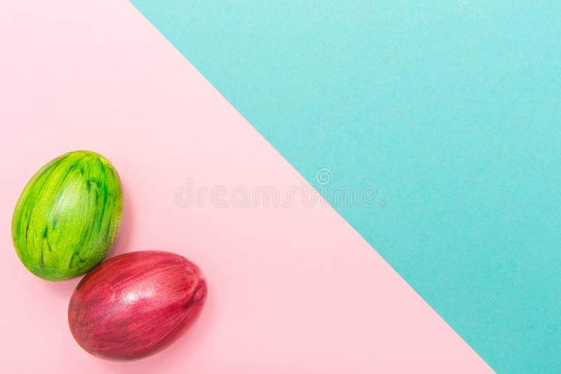 Huevos de Pascua en la turquesa y el fondo geométrico rosado Estilo hecho a mano del huevo verde y rojo nuevo del colorante en un imagen de archivo libre de regalías