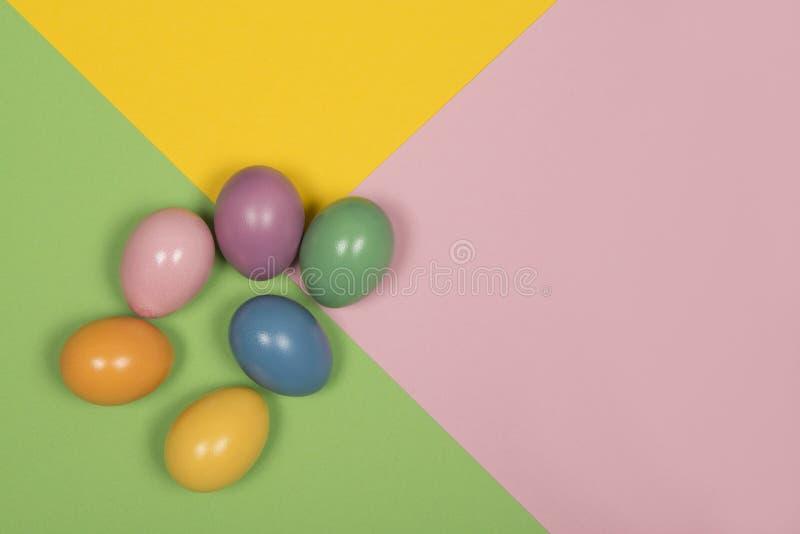 Huevos de Pascua en un fondo coloreado en colores pastel con verde, amarillo y rosado fotos de archivo libres de regalías