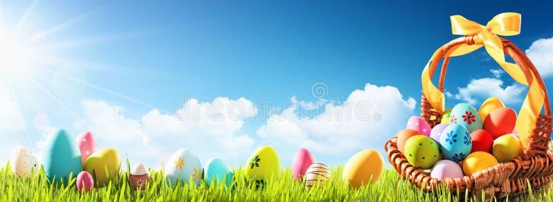 Huevos de Pascua en una cesta en hierba verde fotos de archivo