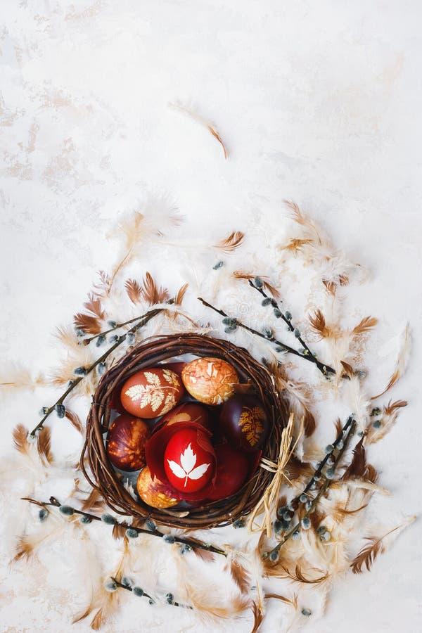 Huevos de Pascua en una jerarquía, teñida naturalmente con las pieles y las flores de cebolla foto de archivo