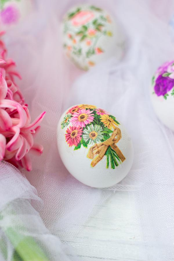 Huevos de Pascua hermosos adornados con las servilletas de papel y las flores en el fondo blanco de Tulle; fotos de archivo