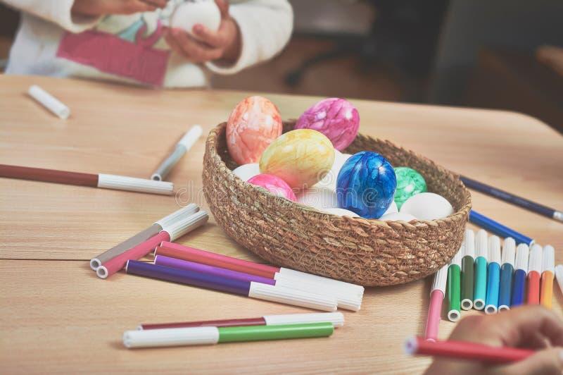 Huevos de Pascua de la pintura de los niños con la ayuda de su mamá y con los marcadores en casa fotografía de archivo
